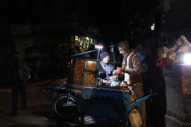 A street food vendor works by the light of a small generator.