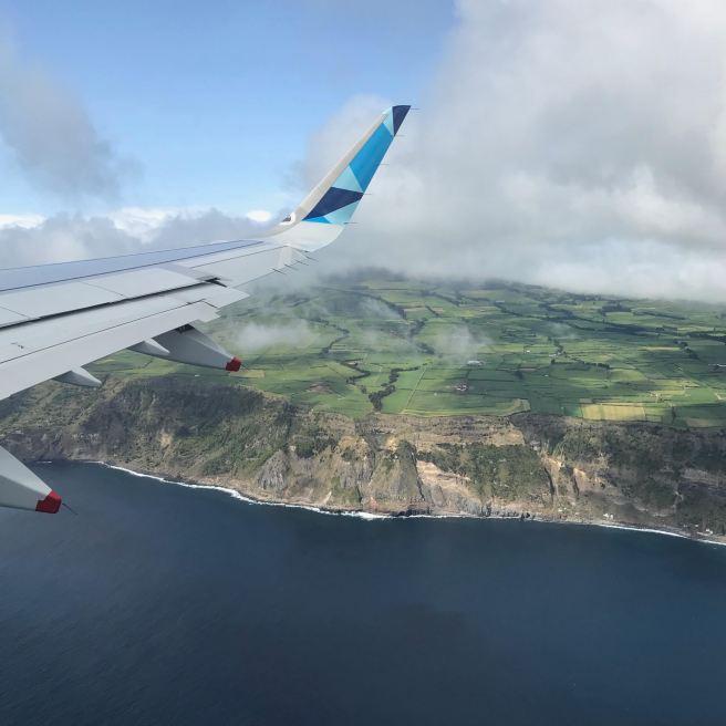 An airplane flies over a green landscape